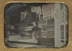 Daguerreotype of a shopkeeper posing behind the counter of a clothing store, location unknown, c. 1840's.