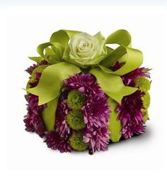 A pave arrangement of fresh flowers in shades of purple and green is designed in the shape of a gift box, then decorated with a green satin ribbon and a rose.
