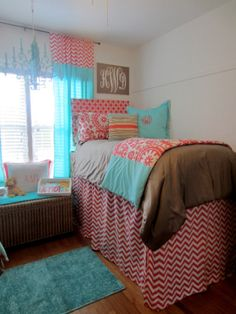 Classy coral and blue dorm room. Love the extra long bed skirt hat hides all the storage below the raised bed. Featured Premier Fabrics: Zig Zag Coral (window panel topper, headboard & bed skirt), Suzani Coral (sham & folded duvet)