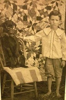 quilt backdrop..(the dog has glasses, and the boy looks none too happy, my guess it's that peter pan collar they made him wear & he wants his glasses back)