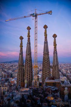 A construction crane rises over the Sagrada Familia Cathedral designed by Antoni Gaudi in Barcelona, Spain.