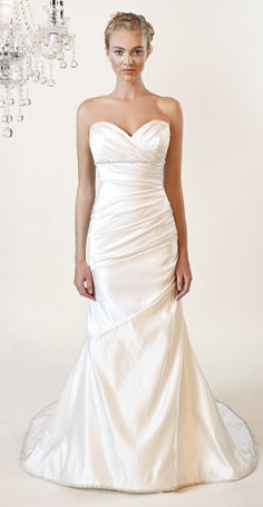 Strapless fit and flair gown with sweetheart neckline. Swarovski crystlal belt and trim along hemline. Shown in diamond white, non-silk versions available.