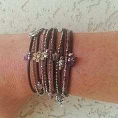 Boho leather wrap bracelet wraps around your wrist three times and can also be worn as a necklace. It is secured with a lobster clasp. FEATURES: *2 cords of dark brown leather *Silver chain *1 strand Miyuki beads in my custom purple mix *Tibetan Beads *Amethyst Chips *4 charms of your