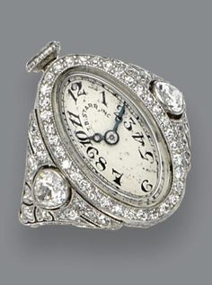 Ring Watch - T.B.Starr (circa.1920) Platinum and diamond's. An oval dial with black Arabic numerals and blued steel moon-style hands framed by single-cut diamonds, the openwork shoulders set with 2 pear-shaped diamonds and additional single-cut diamonds, weighing a total of approximately 1.50 carats, size 6¼, dial signed T.B. Starr, Inc., movement by C.H. Meylan.
