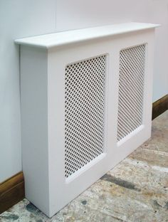 Three-quarter view of a wooden radiator cover with two mesh panels, finished in gloss white