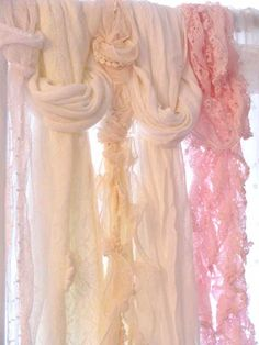Various scarves hung in a window for a glorious display for that windowl