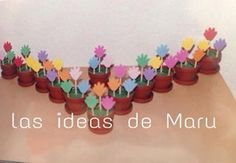Mini macetas de plástico, llevan arena cubriendo con plastilina en color verde, con manitas de fomi realice lo que serian las flores tipo tulipán