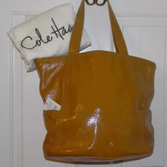 Cole Haan leather purse with dust bag In pristine condition. The color is like a butter squash. There is a tiny pull on the handle Cole Haan Bags Satchels