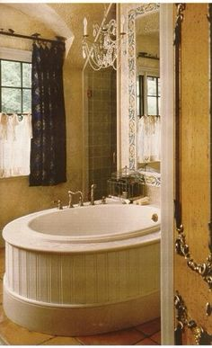 Bead board surround follows the shape of the oval tub, hand painted tile mirror surround, with cafe lace curtains with a hand painted curtain fabric..........the Leo Dowell Signature touch. Leodowellinteriors.com