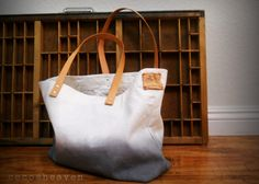 This tote bag by Cocosheaven is handmade with 100% canvas & 100% leather shoulder strap.  Hand dyed in grey with 100% white canvas fabric. A vintage look label is attached in the one side.  Dimension: 19.5 x 12.5 x 5 Strap size: 24 long and 3/4 wide. Inside pocket 9.5 x 5.5