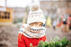 Young girl looking at camera, carrying a Christmas wreath at the market.