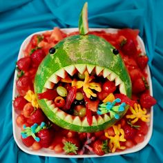 Cute without being too kitschy, transform a watermelon into a scary shark filled with fruit salad, gummy fish, and octopus candies.