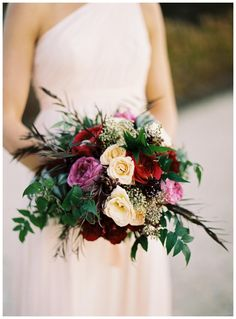 Fall bridesmaid bouquet with florals in ivory, scarlet and amethyst by Beehive Events. Image by Eric Kelley.