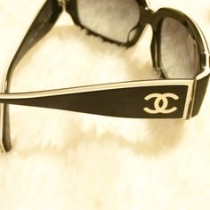 Authentic Chanel Sunglasses Black Chanel sunglasses w white detailing. Purchased at Saks for $312.00. I have original box, including price tag. ($290.00)Comes with lens cloth, protective drawstring bag, sunglass case & info manual. Style number is 5114. There is a scratch in the right lens as I tried to capture in the pic. It is not in the line of vision when I wear them so I never had it repaired. I was told they could be repaired through Luxottica if desired. Priced accordingly due to the…