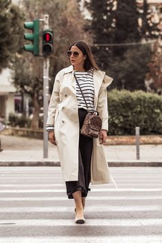 Streetstyle - Stella Asteria wearing classic look with beige trench coat, breton top, Louis Vuitton Palm Springs backpack as a cross body, black denim culottes, Chanel slingbacks and Chloe Carlina sunglasses