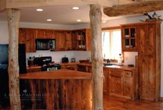 This reclaimed barn wood cabinetry, island and flooring were designed around the rustic log posts and ceiling beam, bringing a natural, outdoors-y feeling to the customer's unique kitchen space. © 2016 E. Braun Farm Tables and Furniture, Inc.™