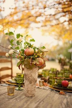 A Fall wedding centerpiece with pomegranates.: