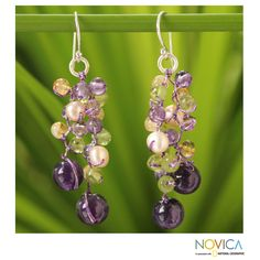 Anusara combines the fresh glow of peridot and citrine with the mystical beauty of amethyst for the design of these earrings. She knots the gems with light purple silk threads, strategically adding cream pearls and glass beads to handcraft these earrings.