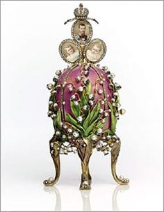 "LILIES OF THE VALLEY EGG, 1898.Inspired by Tsarina Alexandra's favorite flower, the pink enameled egg presented on Easter 1898 is decorated with lily of the valley pearl and diamond-set blossoms. These delicate sprays are nestled among green enameled leaves that conceal a pearl ""button"" that causes the ruby and diamond-set Imperial crown to raise. Hidden beneath the finial is a trio of portraits representing her husband and their 2 eldest daughters, the Grand Duchesses Olga and Tatiana."