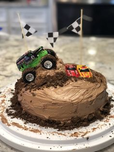 Monster truck cake. Used a hot dog bun cut in half to make ramp, and crushed chocolate graham crackers for dirt. For the banner I used wooden skewers and glued cut out scrapbook paper to string. Ran the truck tires through frosting to add tire mark effects. Festa Monster Truck, Monster Truck Cupcakes, Monster Truck Birthday Cake, Monster Trucks, 3rd Birthday Cakes, Cars Birthday Parties, Monster Jam Cake, Lego Parties, Lego Birthday