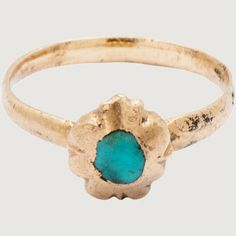 """Italy?, 15th century Gold and turquoise Weight 1.3 gr; bezel 6 x 7 x 4 mm; circumference 39 mm; US size 1¼; UK size B½ This tiny """"pinkie"""" ring is set with a cabochon turquoise, mined in Persia and protecting against sickness and falls from horseback. The ring resembles a diminutive flower that encircles the bud or stone. This type of ring was quite popular existing in silver gilt versions as well as more deluxe gold examples. Description Bezel in shape of a flower set with a cabochon…"""