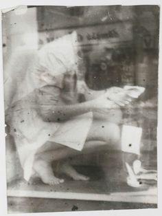 Una commessa piegata nella vetrina di un negozio a curare un dettaglio.. e dentro di lei, concentrata, la grazia di tutte le donne che si piegano su qualunque cosa con amore.   distrattamente donna  Foto di Miroslav Tichy