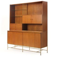 Etagere By Paul McCobb | An elegant modernist etagere of rectilinear form in mahogany and brass having a lower cabinet with folding doors resting on square brass legs and supporting an upper cabinet with doors, glass shelves and drawers.