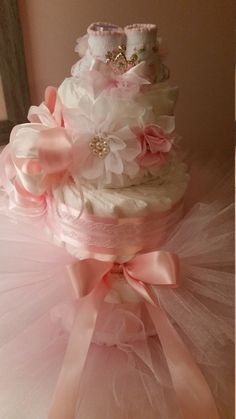 NOTE: (Due to limited supplies of unique craft items the style headband and booties/socks design will vary but always compliment your cake.) This gorgeous cake is the perfect centerpiece for your babys room or shower table-scape. You will receive: -One 3 Tier Diaper Cake approximately/ 65 diapers in Pampers Swaddlers Size 2. -Top Tier has a Tiara Clip on Pink Tulle Pom Pom, and Baby Booties Size 0-to 12 months behind (style will vary but always coordinate beautifully!) -One Gorgeous…