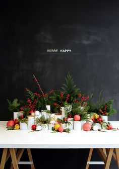 A festive yet simple (and inexpensive) holiday centerpiece made of shipping tubes, ornaments spray painted in matte paint, red berries and scraps of greenery from a neighborhood Christmas tree lot.