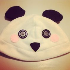 A panda beanie/plushy hat! It's made out of soft, kind of stretchy polar fleece! The blush marks, and nose are made out of felt, and is securely hot glued on. The eyes are black buttons, and are also securely affixed with hot glue.    The hat would fit on a head with an approx. circumference of 5...