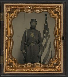 [Unidentified soldier in Union uniform and Company H cap with bayoneted musket, cap box, and Volunteer Maine Militia (VMM) belt buckle in front of American flag] (LOC)