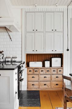 Lovely vintage style drawers and wood panel contrasted with white painted bricks and black marble countertop