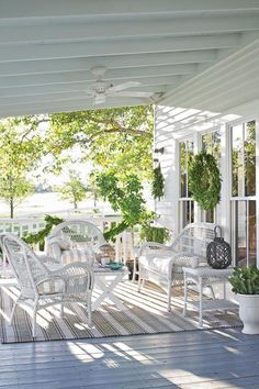 The Porch with a View Reveal - Stunning Farmhouse Before-and-After Makeovers - Southernliving. A fresh coat of paint, including a traditional light blue ceiling, refreshed the porch. White wicker furniture provides a comfortable spot for taking in the views.