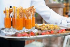A tray of grilled cheese and tomato soup cups and appetizers for a traditional wedding reception.