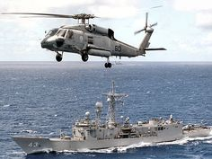 "Sikorsky  HH-60H Seahawk from the ""Golden Falcons"" of Helicopter Anti-Submarine/Combat Search and Rescue Squadron Two (HS-2) flies past  USS ""Thach"" (FFG 43) Oliver Hazard Perry class frigate ,05 September 2001"