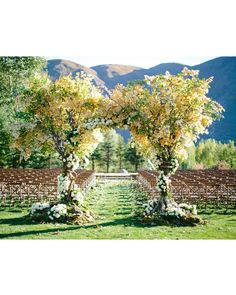 The majestic mountains behind the altar served as the main focal point of the ceremony. Wood chairs were set with Aspen leaves strewn along the aisle instead of a runner. Guests (and the bridal party) entered through an arch made from two trees and elegant white roses.