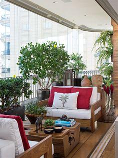 O fechamento com vidro torna confortável a permanência aqui em qualquer estação. Do paisagismo fazem parte a planta-jade (Crassula ovata) (1) e a clúsia (Clusia fuminensis) (2). Mesa de centro da Tora Brasil, sofás da L'Oeil e almofadas da Nani Chinellato (estampada) e Dell'Abitare (vermelhas).