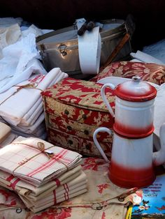 French flea market near Avignon.....vintage floral curtains, an enamel coffee pot, vintage checked tea towels… the sweet little jewellery drawers covered in red toile… & red vintage embroidered napkins.