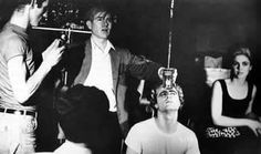 Billy Name with light meter (left) helps Andy Warhol  prepare a shot for Vinyl with Gerard Malanga  and Edie Sedgwick (seated) 1965