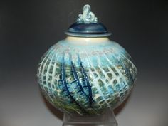 """Wheel thrown with tinted sodium silicate. Wheel thrown lid with sculpted knob. Colors: Stormy Blue, Turquoise, Green, Opal Size: 7.5""""H x 7.5""""W"""