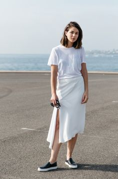 Sara Donaldson wears a white wrap skirt with a white t-shirt and black platform slip on shoes.