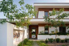 שביל הכניסה מלווה את הבית - מימינו אדנית בנויה, משמאלו גינה ומולו, בניצב לדלת הכניסה, קיר עם נישה גדולה, שבה נתלתה עבודת אמנות ( צילום: מיקאלה בורסטאו )