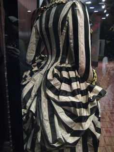 "back of the Striped Masquerade Gown, pleated in the en fourreau style, in the Sweeney Todd movie, courtesy of photo contributor ""Freya"" to The Costumer's Guide to Movie Costumes __"