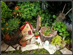 """Un rincón del jardín: piedras pintadas, topiarios, troncos reutilizados como maceteros, y mucho verde. Casi un jardín de hadas. * """"Almost a fairy garden"""": painted stones, stumps upcycled as planters, topiaries an lots of green!"""