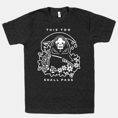 """Don't fear the reaper with this Grim Reaper t-shirt. This graphic tee features an illustration of The Grim Reaper holing it's Death Scythe surrounded by flowers and the phrase """"This Too Shall... 