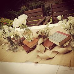 Rustic country wedding flowers featuring books, hessian runners and tea lights with ivory blooms
