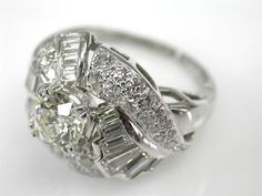 Vintage Cluster Ring: One custom-made platinum ring. One old European cut diamond (0.91 carats: VS1 clarity: I-J colour). Eighteen straight and tapered baguettes ...