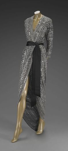 1980's evening dress: This dress was designed by Halston in 1981. Evening dress for women in the 1980's consisted of elaborate and glamorous dresses with sequins and beads and classy cuts and silhouettes.