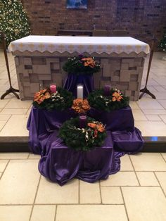 2015 Advent Wreath We used four boxes with 8 wreaths to create the effect. Clear hurricane candle holders were filled with candles. We drilled out the center of the candles and inserted votives so they could be reused year after year.
