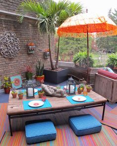 Tropical takeout. Order in from your favorite local restaurant and focus your effort on the decor.  A coffee table placed on colorful outdoor mats and surrounded with floor cushions makes a fun spot for a small dinner party to congregate at. Set out colorful parasols, lanterns, potted succulents and sculptures or other artwork borrowed from inside.